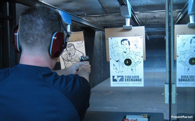 mężczyzna na krytej strzelnicy strzela do tarczy