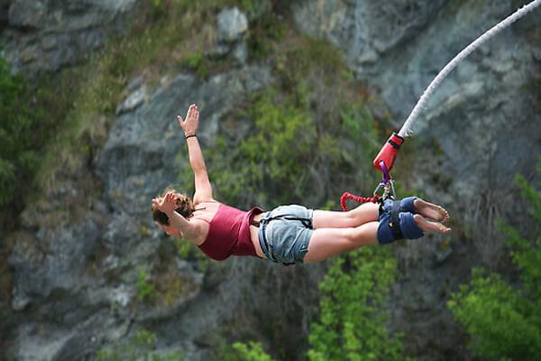 Kobieta podczas skoku na bungee z rozłożonymi rękoma