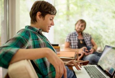 Kobieta korzystająca z laptopa, oraz mężczyzna trzymający kubek