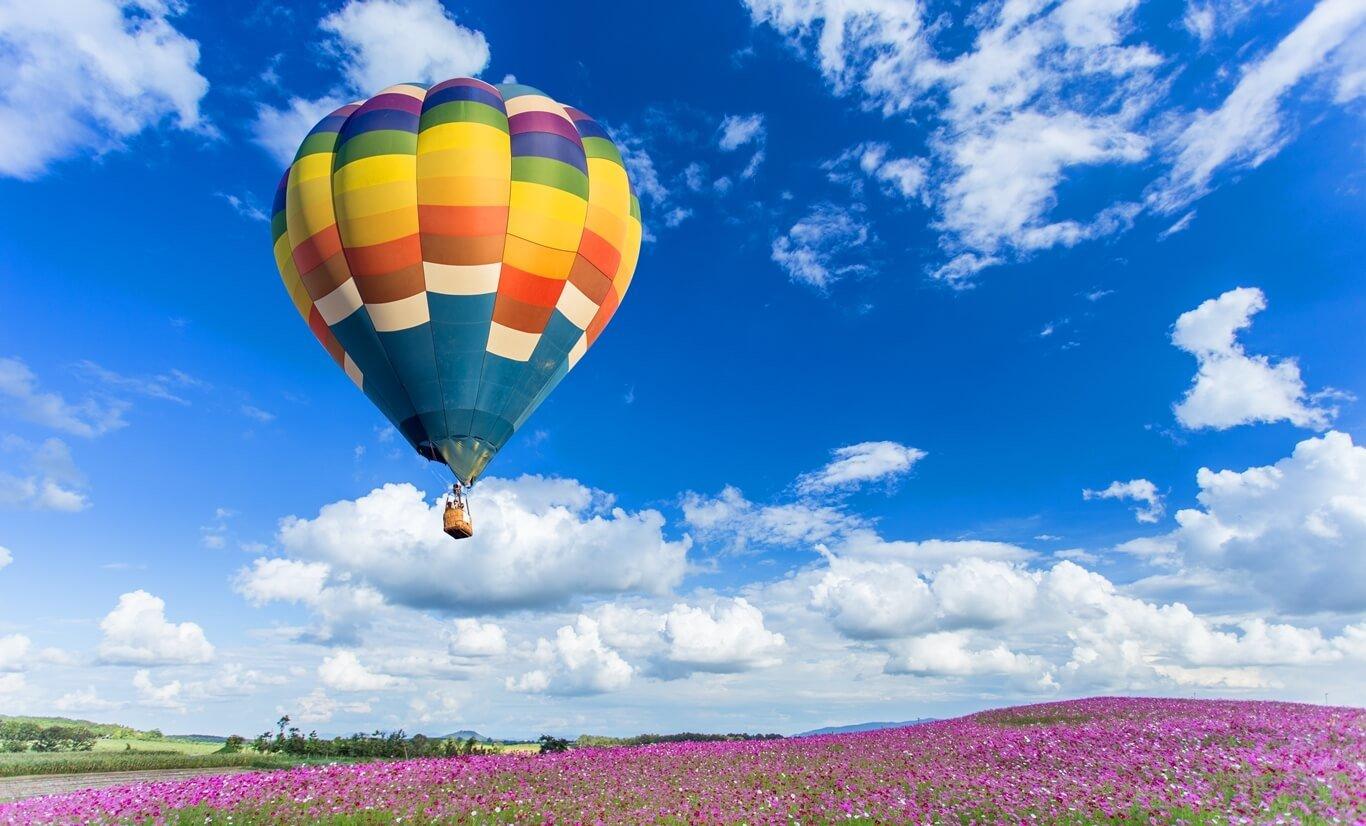 lot kolorowym balonem nadkwitnącą łąką