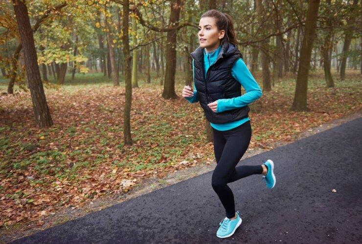młoda kobieta biega jesienią po parku