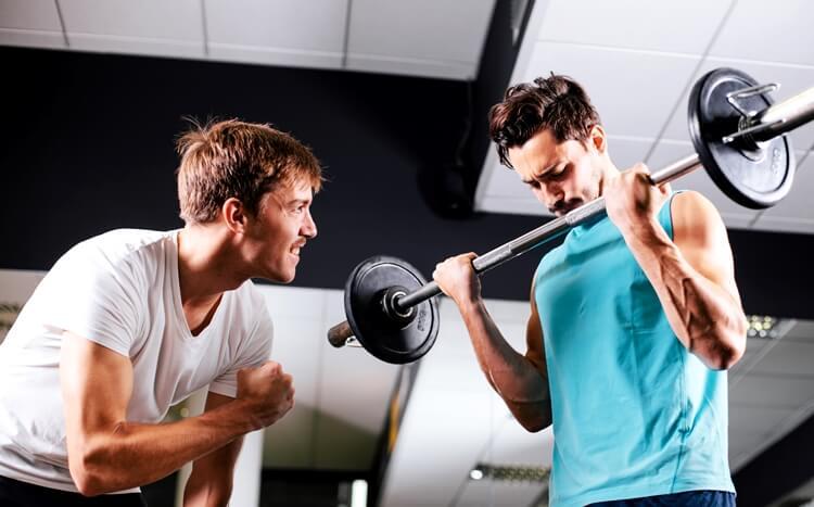 mężczyzna ćwiczy nasiłowni podokiem trenera