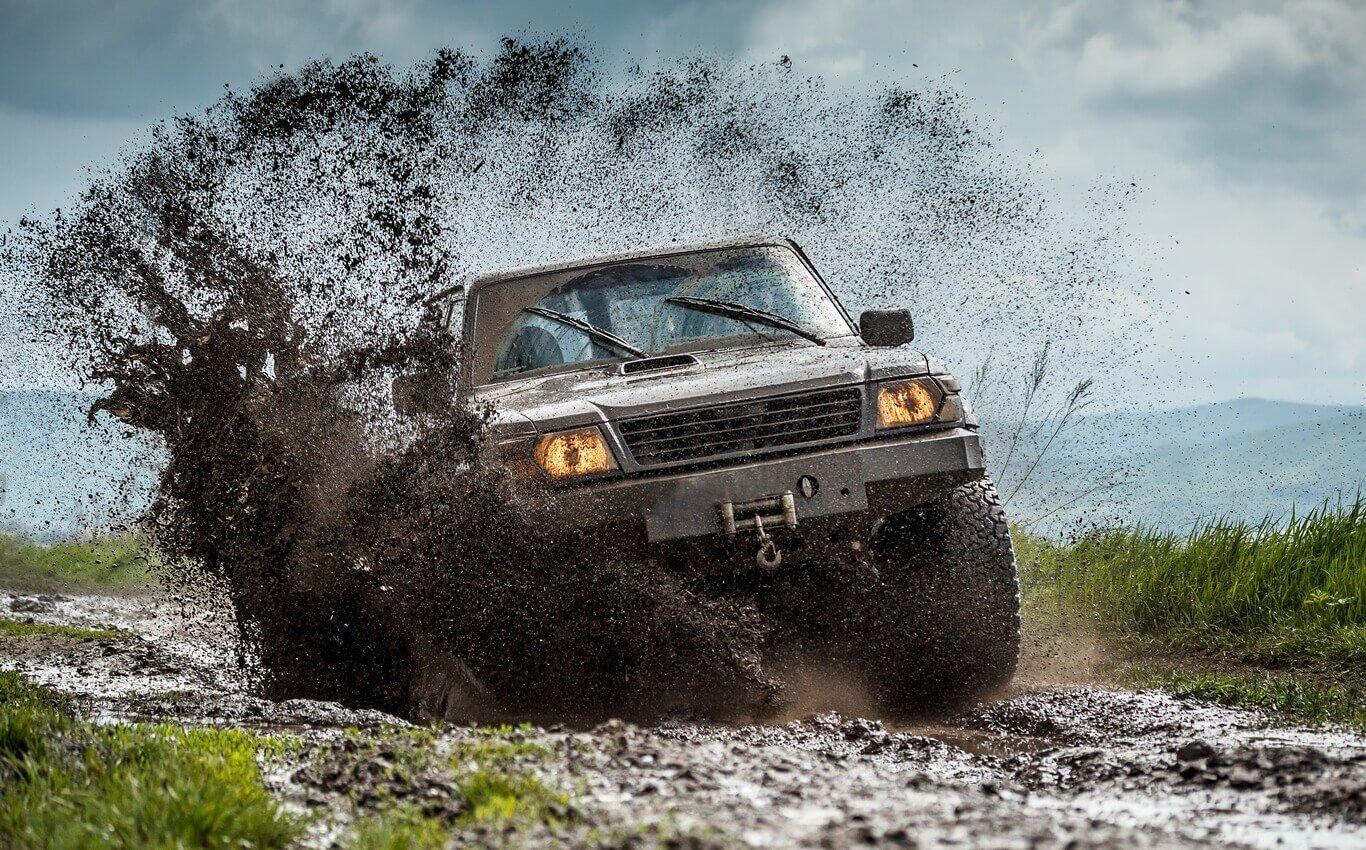 samochód terenowy pokonuje przeszkody wbłotnistym terenie