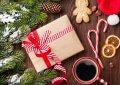 gałązki choinki, szyszka, prezent, candy cain i kubek z kawą na tle ciemnego drewna