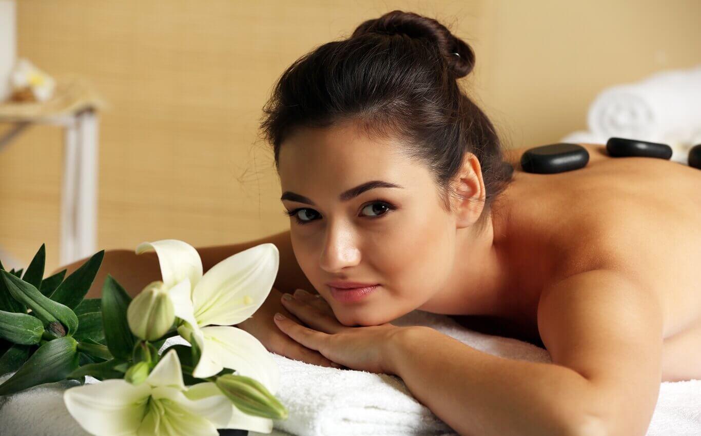 piękna młoda kobieta na masażu pleców gorącymi kamieniami