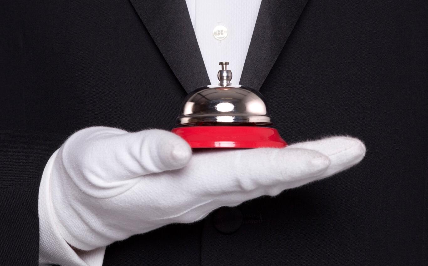 mężczyzna wbiałej rękawiczce trzyma nadłoni dzwonek