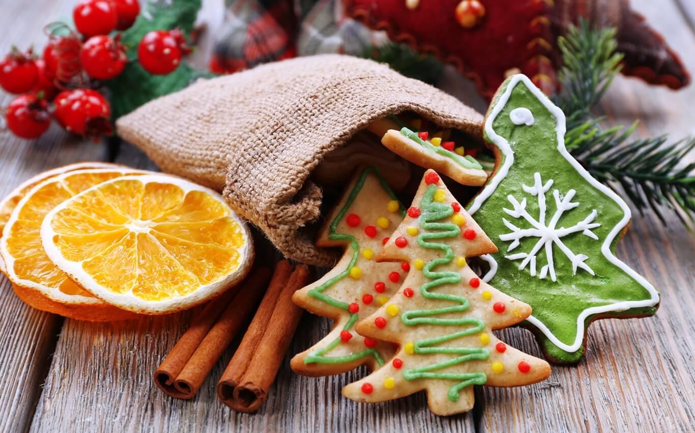 kolorowe pierniczki plater pomarańczy i laski cynamonu na drewnianym tle