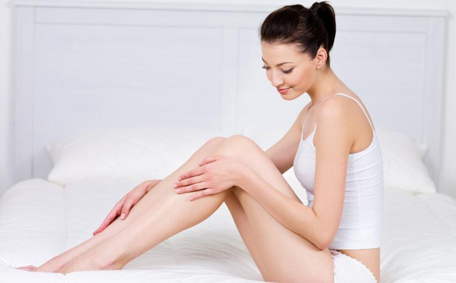 piękna młoda kobieta siedzi nałóżku igładzi swoje długie nogi