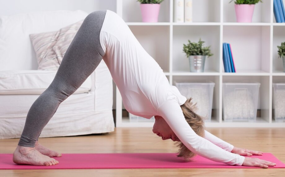 kobieta wśrednim wieku ćwiczy jogę wdomu