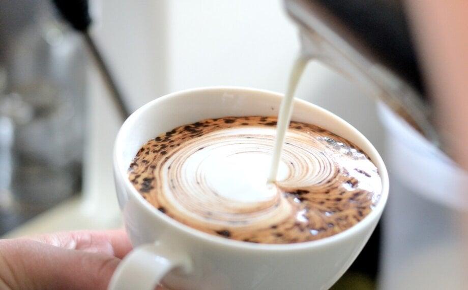 barista dekoruje kawę spienionym mlekiem