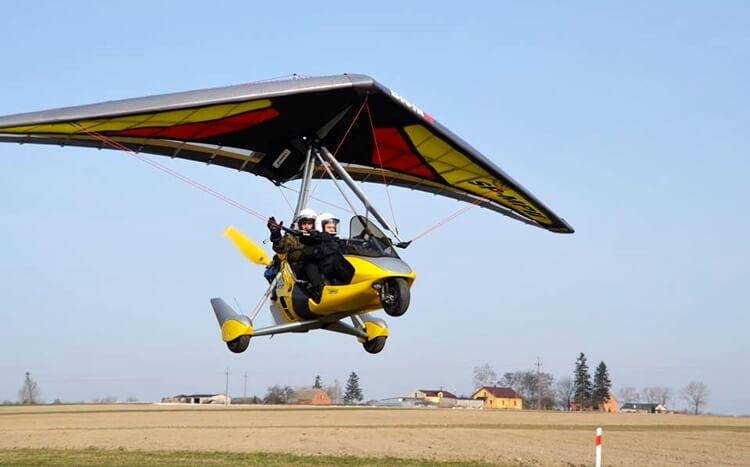 żółta motolotnia leci nadpolami