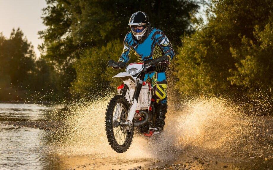 mężczyzna jadący motocyklem przezwodę