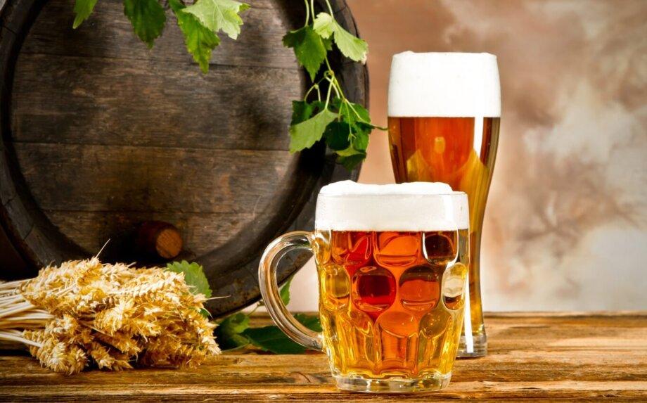 szklanka i kufel piwa na tle drewnianej beczki