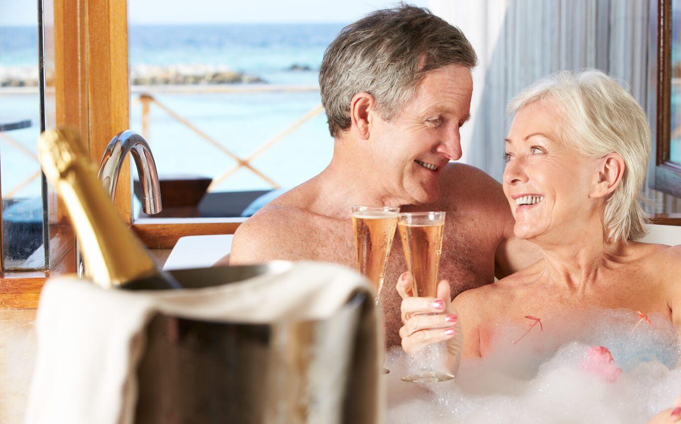 małżeństwo wśrednim wieku relaksuje się wjacuzzi zlampką szampana