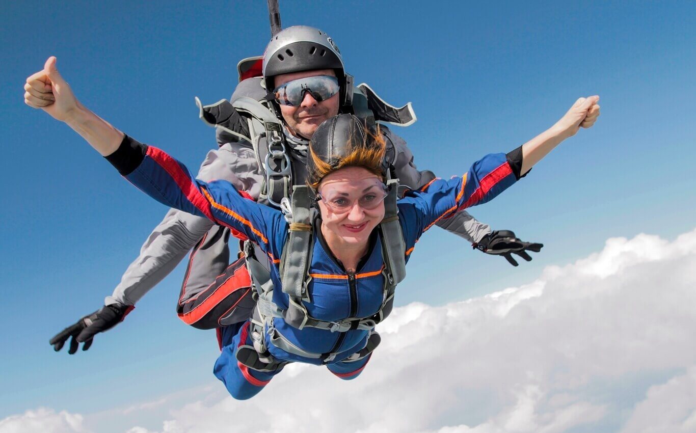 kobieta i mężczyzna oddają skok ze spadochronem w tandemie