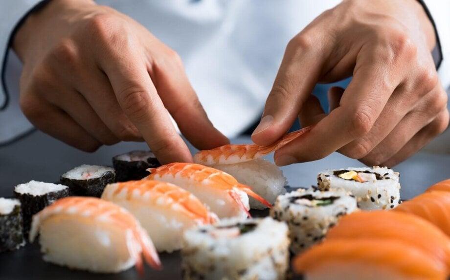 mężczyzna przyrządza sushi