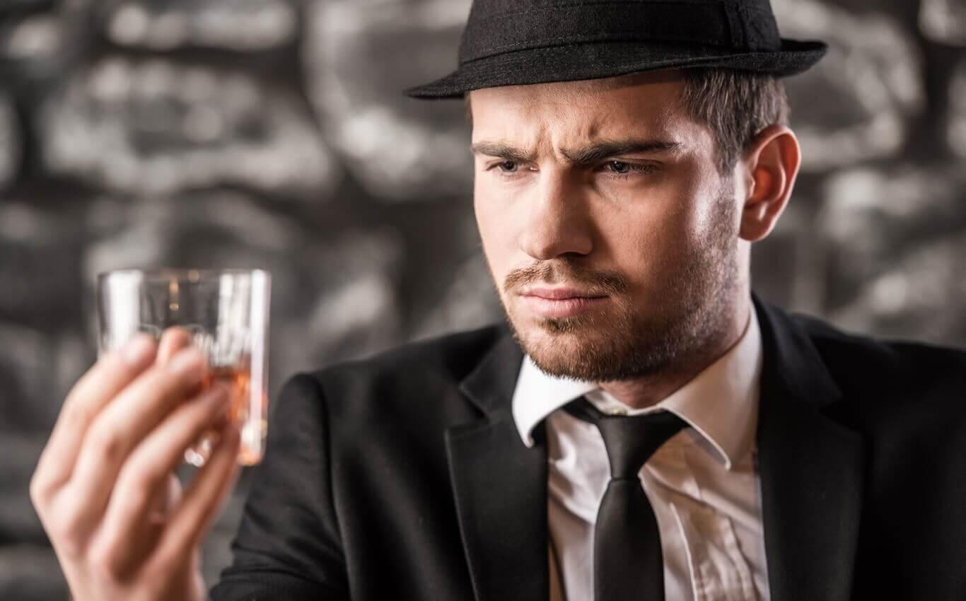 elegancko ubrany mężczyzna degustuje whisky