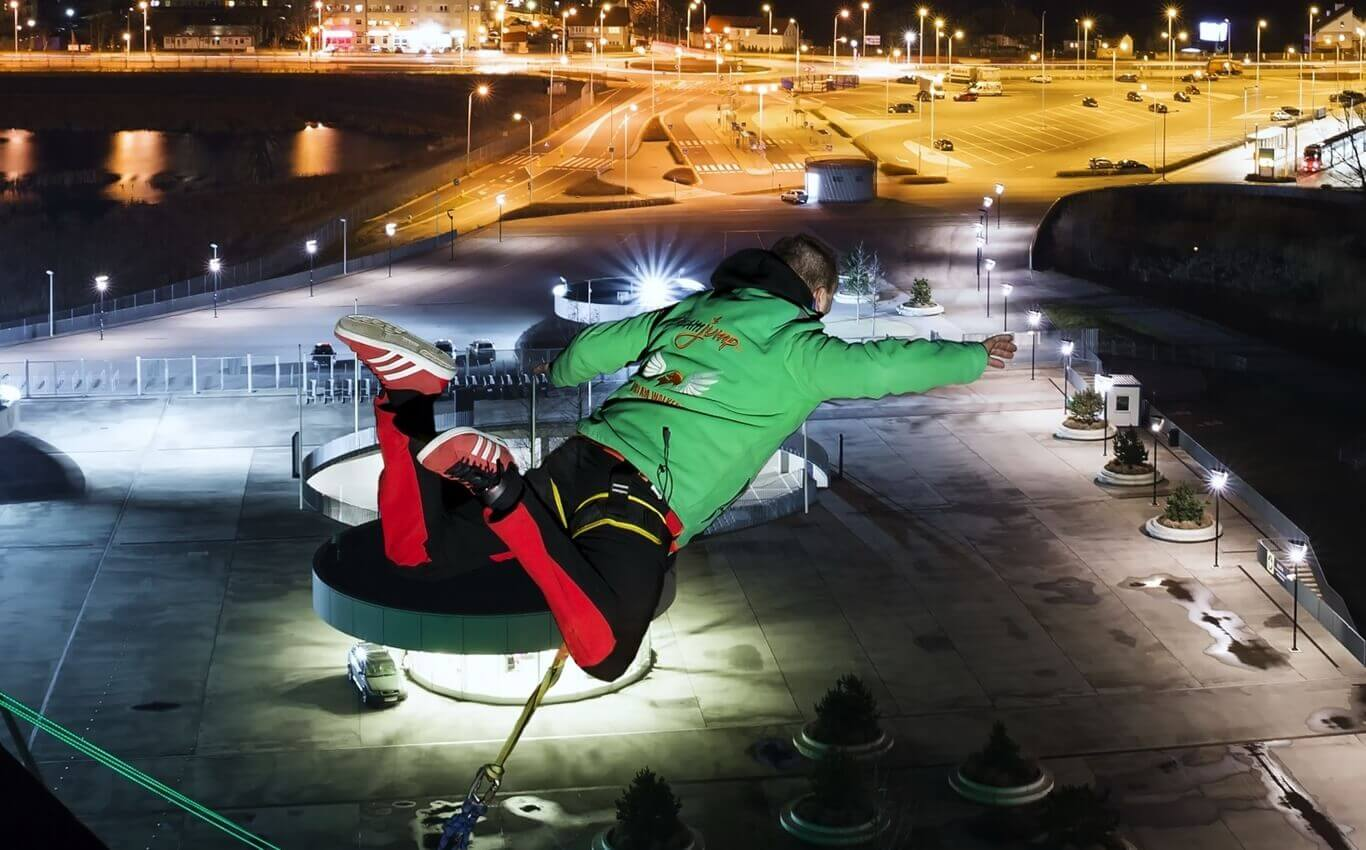 młody mężczyzna oddaje skok dream jump nocą