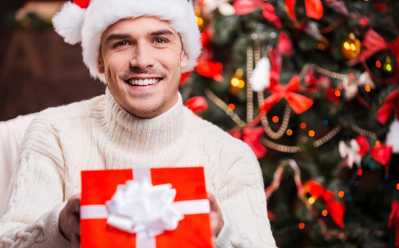 przystojny młody mężczyzna w czapce mikołaja otwiera prezent