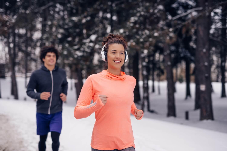 kobieta i mężczyzna biegną po śniegu
