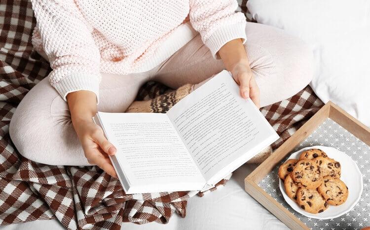 kobieta czyta książkę siedząc na łóżku