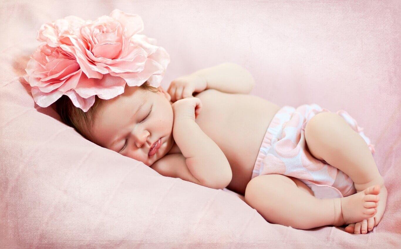 noworodek zdużym kwiatem naróżowym tle