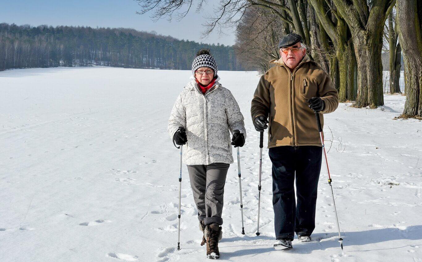 seniorzy uprawiający nordic walking zimą