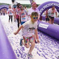 Młody chłopak biegnący podczas biegu przezpianę, wtle inni uczestnicy