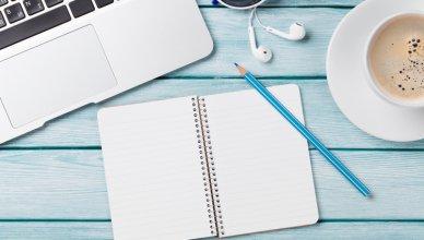 zeszyt, ołówek i laptop na niebieskim tle