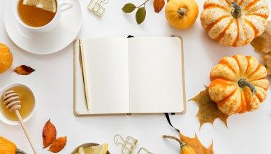 zeszyt, herbata z cytryną, miód, dynie i jesienne liście na białym biurku
