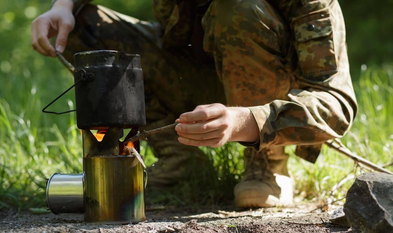 mężczyzna w lesie podgrzewa garnuszek na ogniu