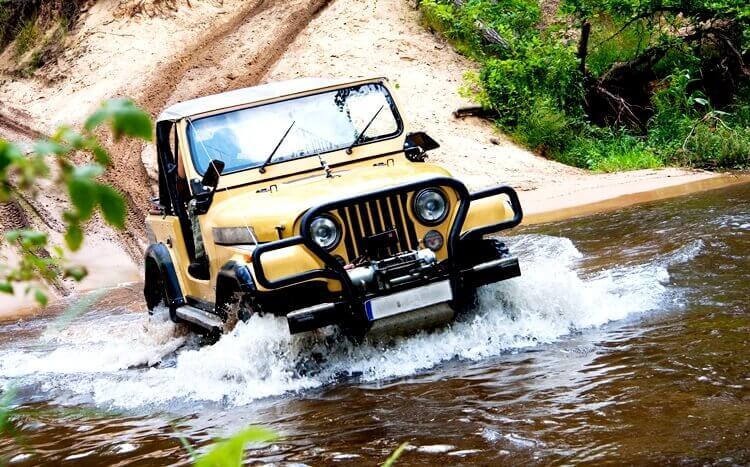 samochód terenowy przeprawia się przez rzekę