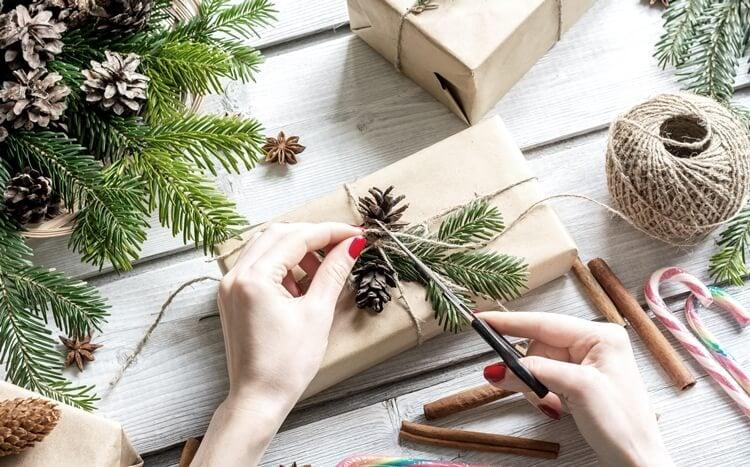 kobiece dłonie pakują prezent na święta