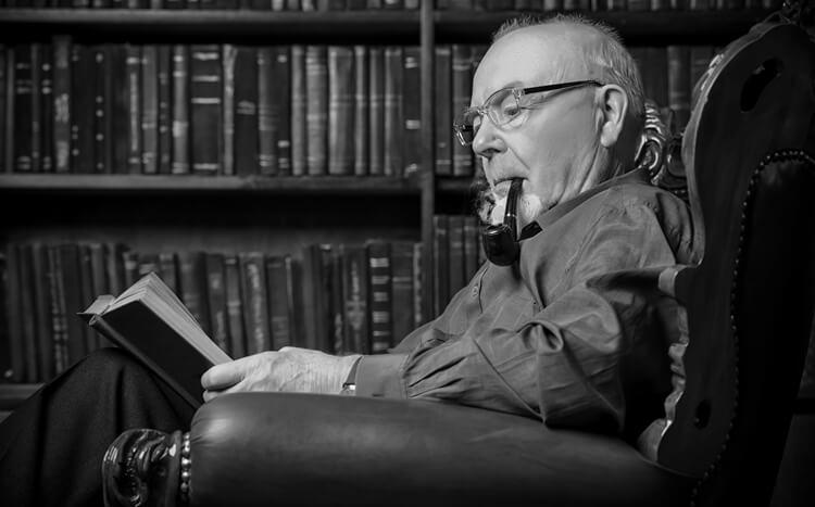 starszy mężczyzna siedzi w fotelu, czyta książkę i pali fajkę