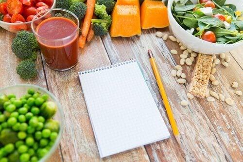 Notes z ołówkiem znajdujący się na drewnianym stole, wokół zdrowe jedzenie