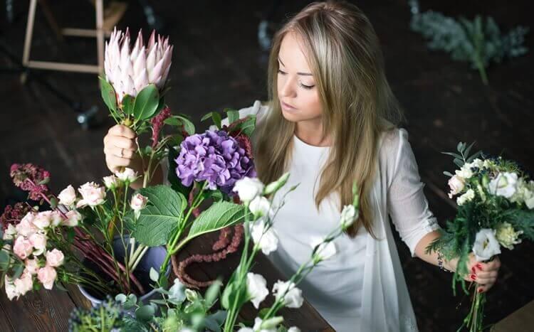 młoda kobieta układa kompozycję zkwiatów
