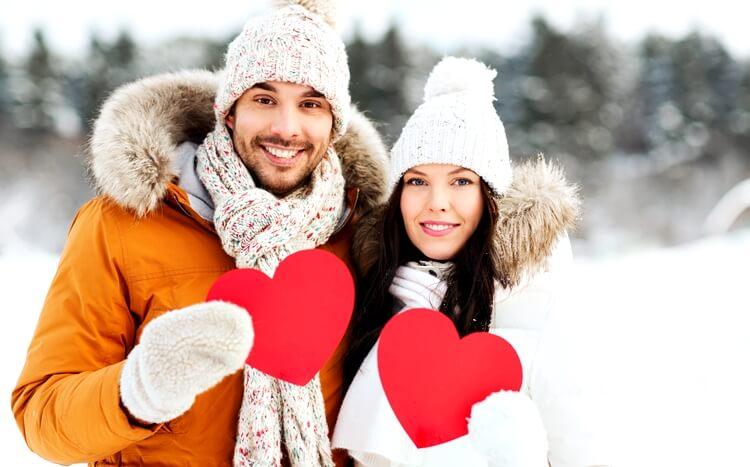 szczęśliwa para z czerwonymi serduszkami na tle śniegu i lasu