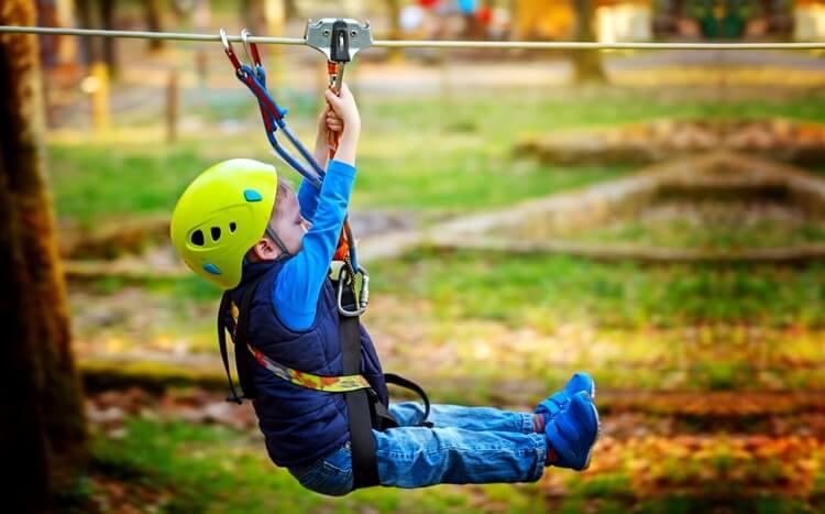 chłopiec zjeżdża natyrolce wparku linowym