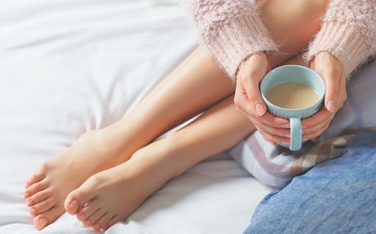nogi kobiety siedzącej na łóżku z kubkiem kawy w dłoni