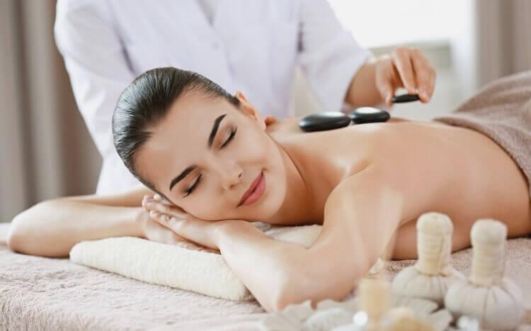 zrelaksowana kobieta namasażu gorącymi kamieniami wgabinecie spa