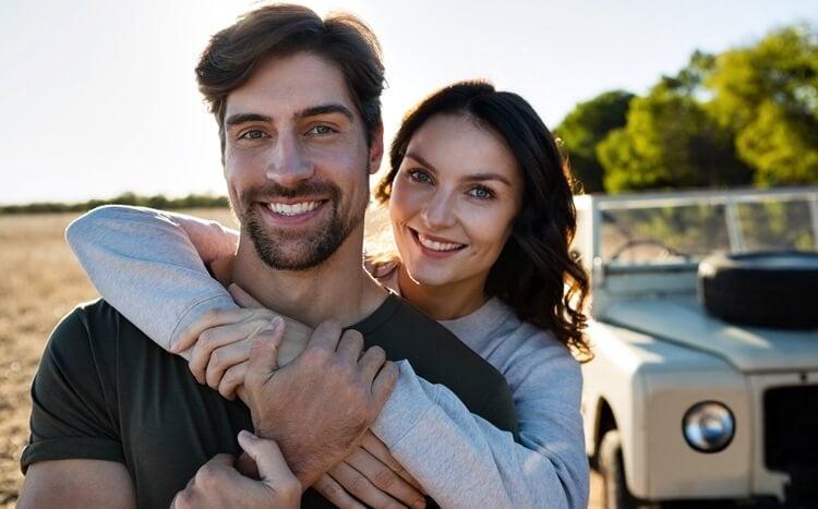 usmiechnięte małżeństwo natle samochodu terenowego