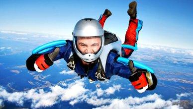 mężczyzna pokazuje uniesione w górę kciuki podczas skoku ze spadochronem