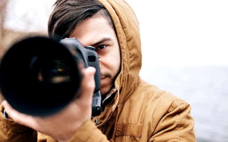 przystojny młody mężczyzna zaparatem fotograficznym