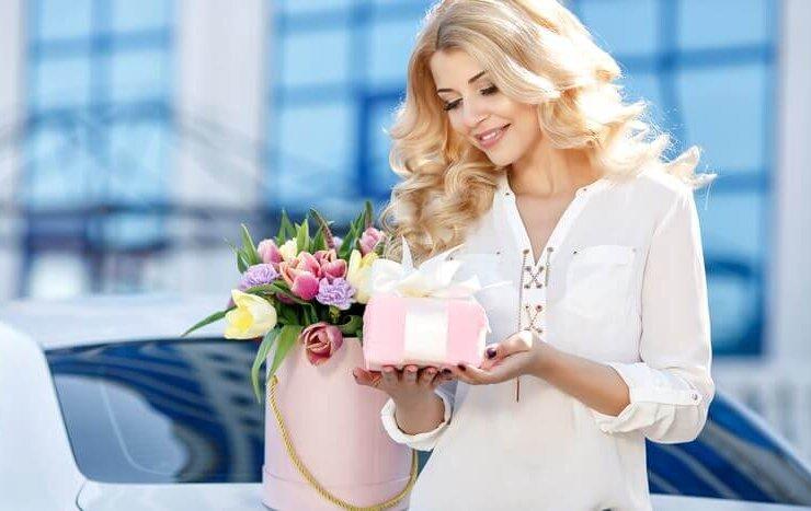 Kobieta ubrana na biało trzymająca w rękach prezent oraz kwiaty