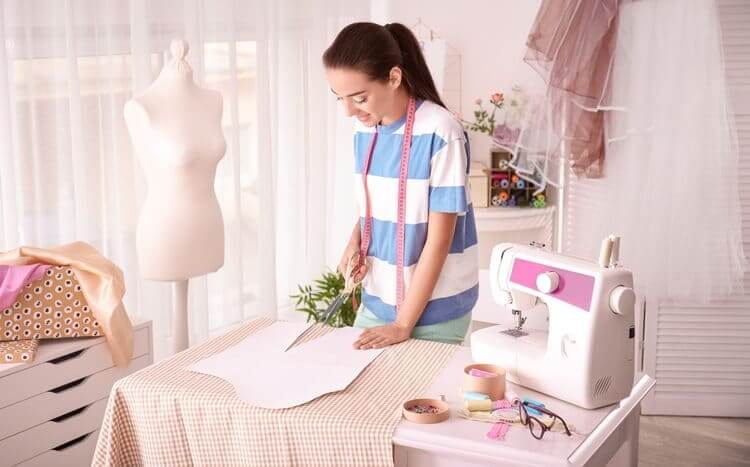 młoda kobieta szyje ubrania