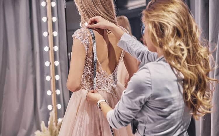 krawcowa mierzy sukienkę na modelce