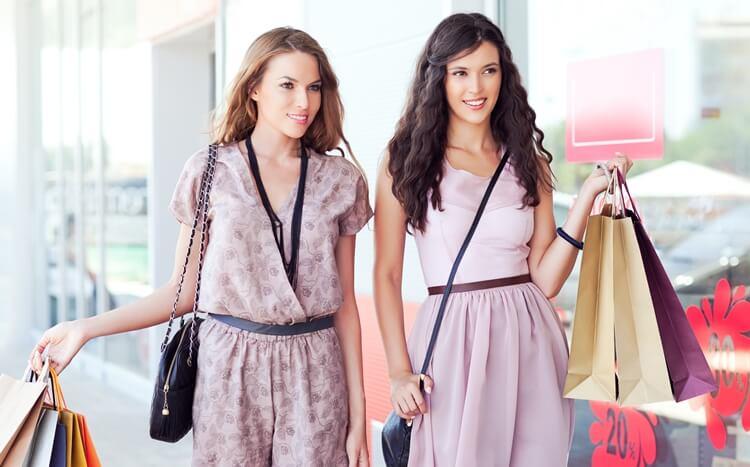 dwie piekne, młode kobiety niosą torby z zakupami