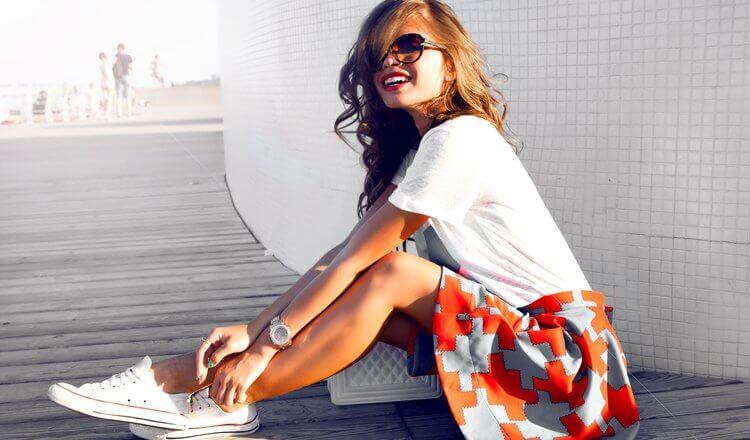 młoda modnie ubrana dziewczyna w t-shircie, spódnicy i białych conversach