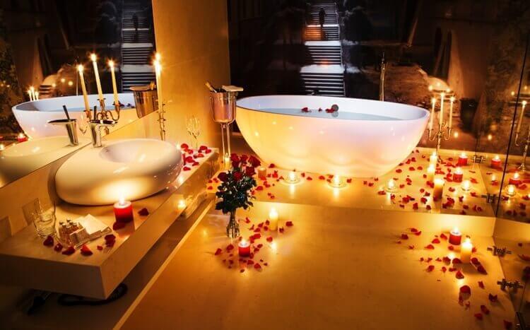 łazienka wpokoju hotelowym zwanną, świecami ipłatkami róż