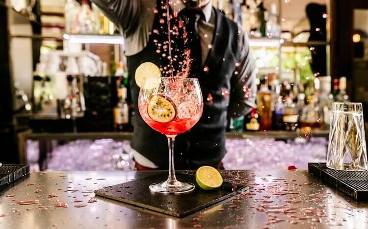 barman przygotowuje kolorowego drinka z limonką i marakują